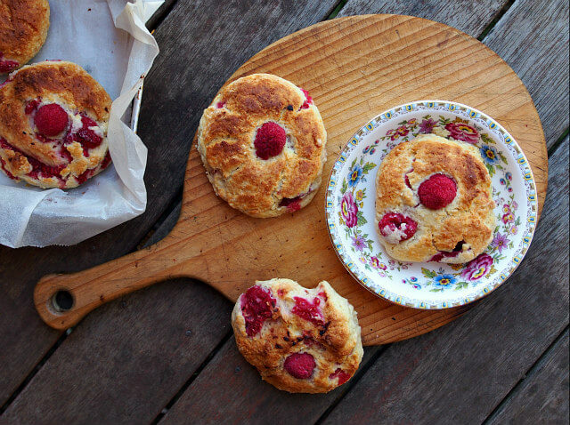 overhead view of gluten free raspberry scones on a flowered plate and wooden cutting board
