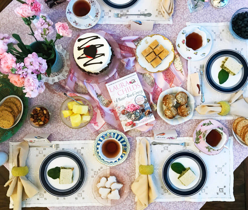 overhead view of a tea party tablescape with place settings with pink floral tablecloth, tea cups, tea sandwiches, cake, cookies, pink flowers, and Laura Childs' book Plum Tea Crazy
