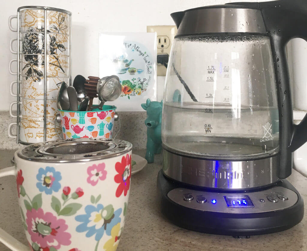 a clear electric kettle boils next to a floral mug with tea infuser, while more mugs and tea spoons wait in the background.