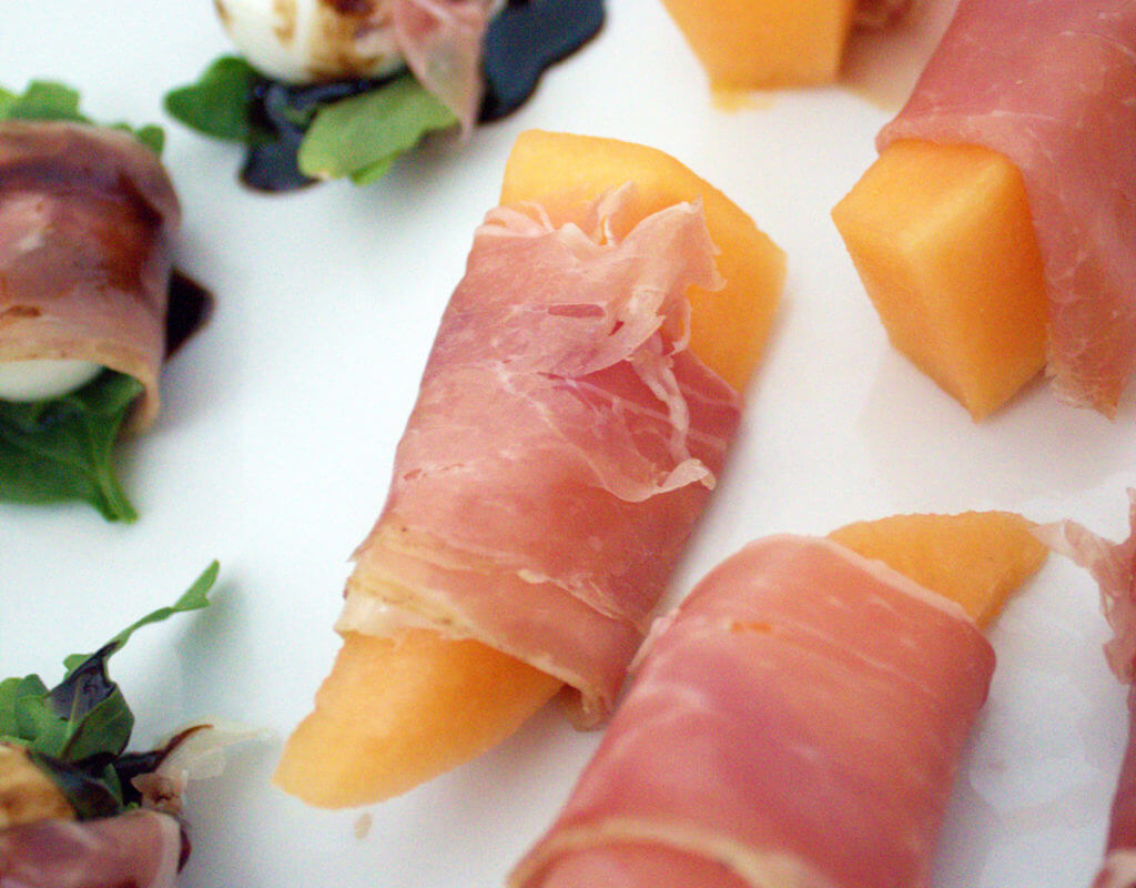 Closeup view of a piece of cantaloupe melon wrapped in prosciutto.