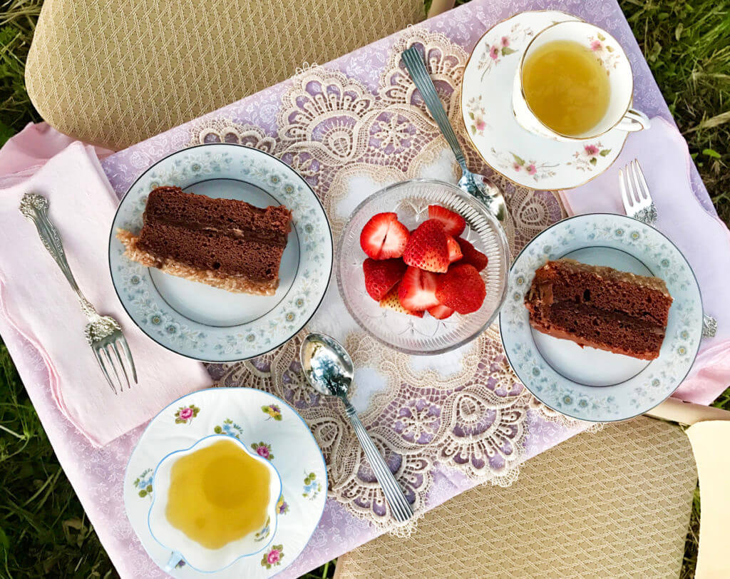 Overhead view of a garden tea party with teacups, cake, and strawberries on a pink lace tablecloth.