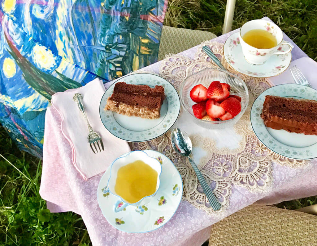 Overhead view of a garden tea party with teacups, cake, and strawberries on a lace tablecloth.