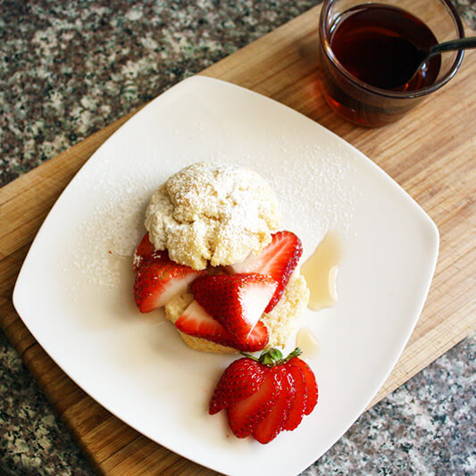 Overhead view of a fruit shortcake with fresh strawberries, dusted with powdered sugar on a white plate. A cup of sugar plum tea syrup sit next to it on a wooden board.