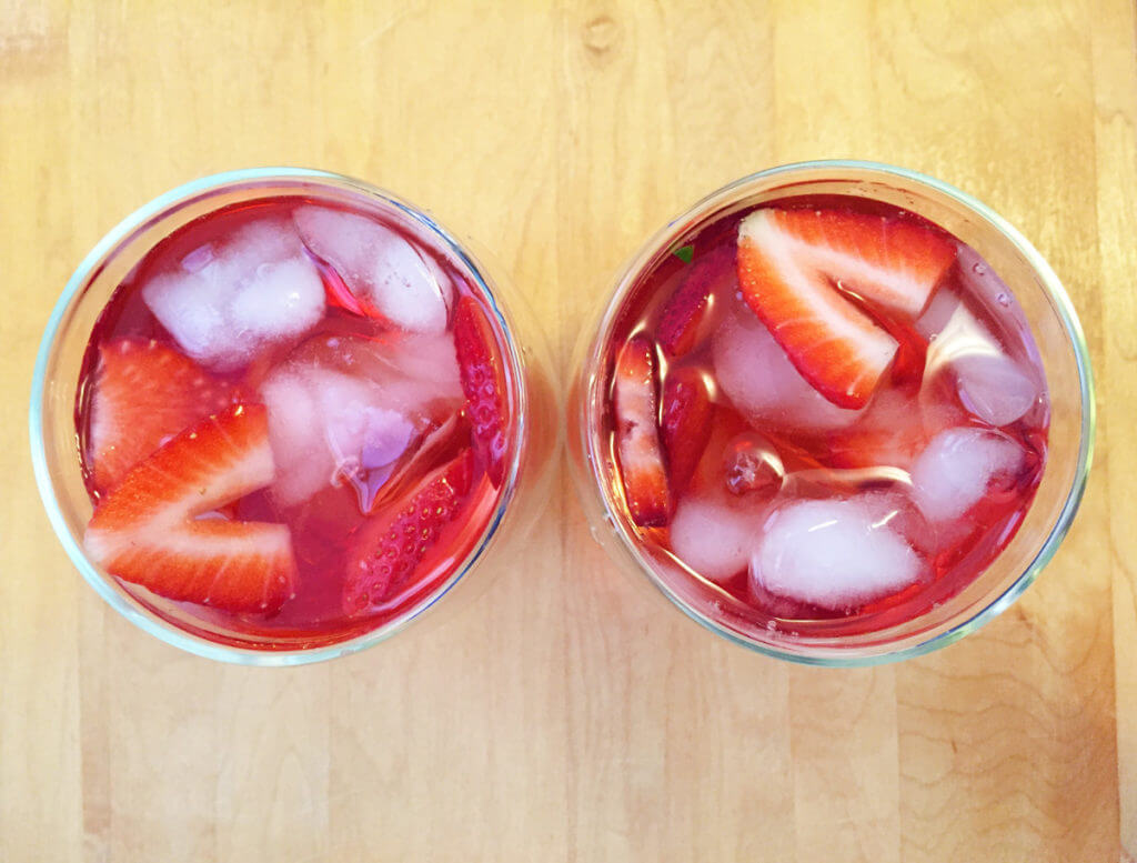 overhead view of two glasses of red iced tea with ice cubes and fresh strawberries on a wooden background.