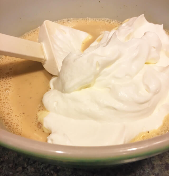 Whipped cream is folded into the milk and tea mixture.