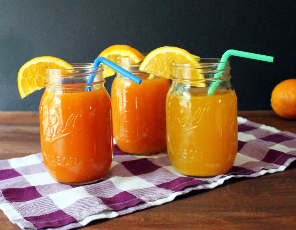 A trio of tea and orange juice drinks sits on a checkered cloth.