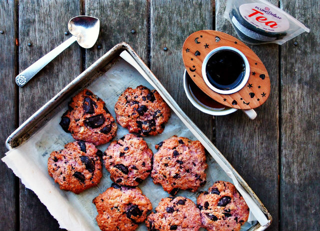 Baked scone cookies sit on a tray next to a cup of loose leaf tea.
