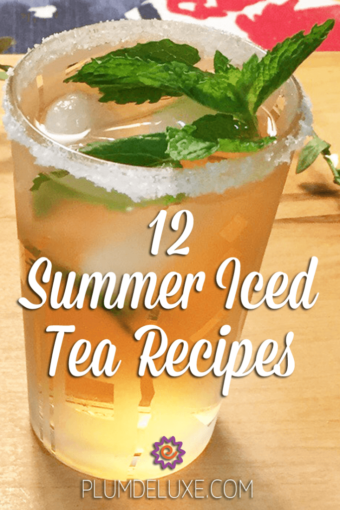 A glass of Moroccan mint iced tea with a sugared rim and a spring of fresh mint sits on a wooden board.