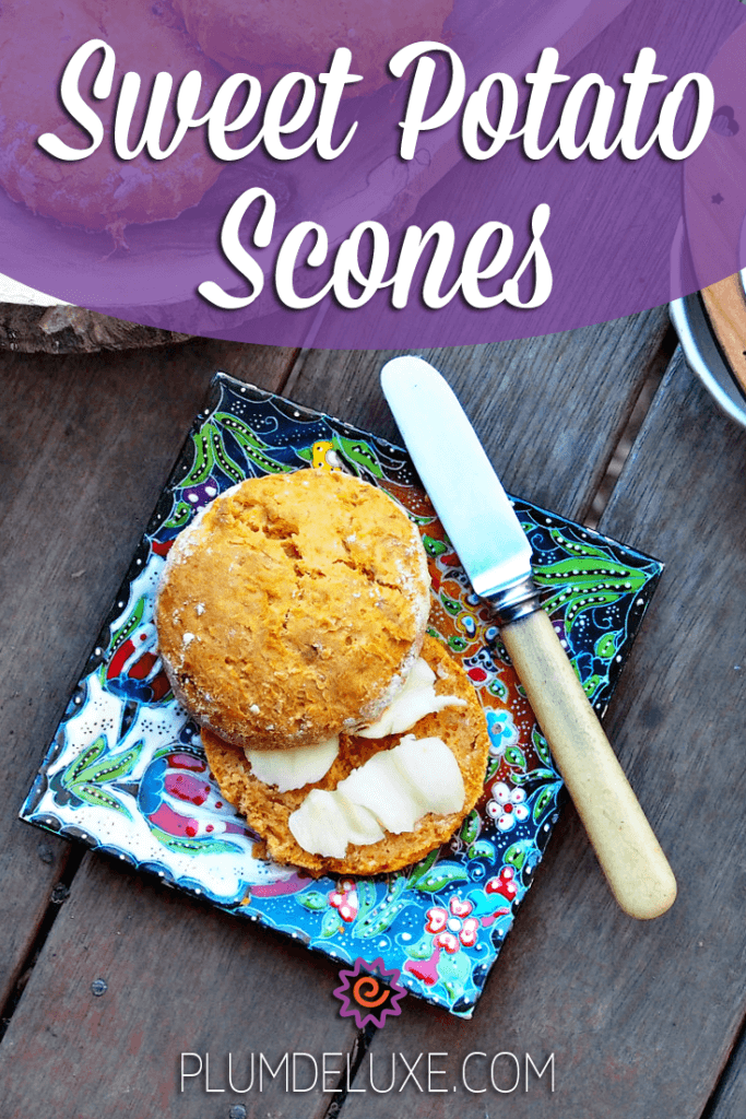 Overhead view of a sweet potato scone split in two and slathered with butter.