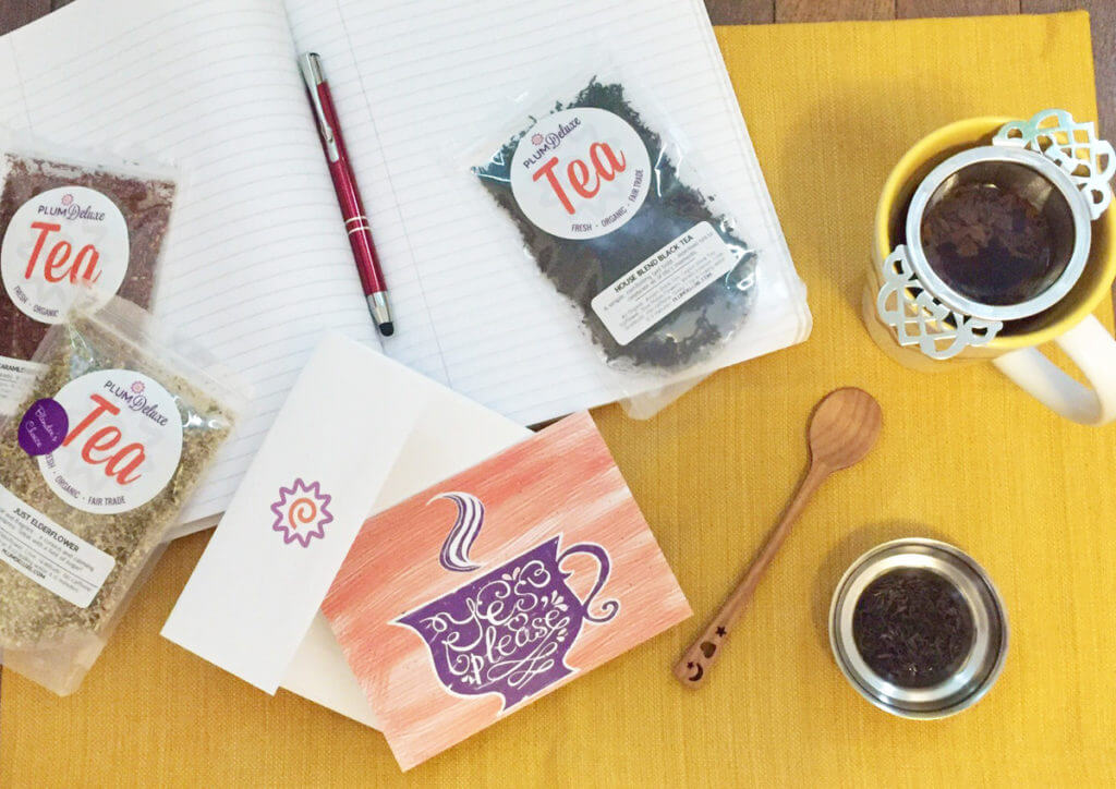 Overhead view of loose leaf tea, a teaspoon, a cup of tea, a note card, and a journal on a yellow mat.
