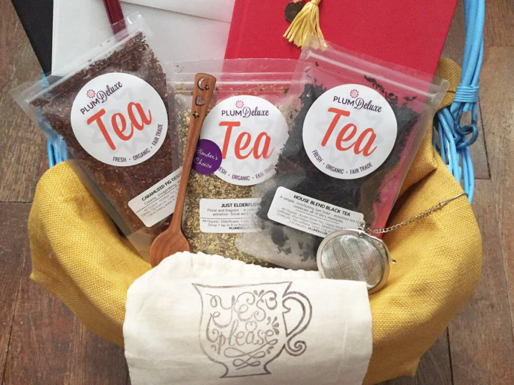 A trio of loose leaf teas, teaspoon, tea infuser, and other treats are tucked into a gift basket.
