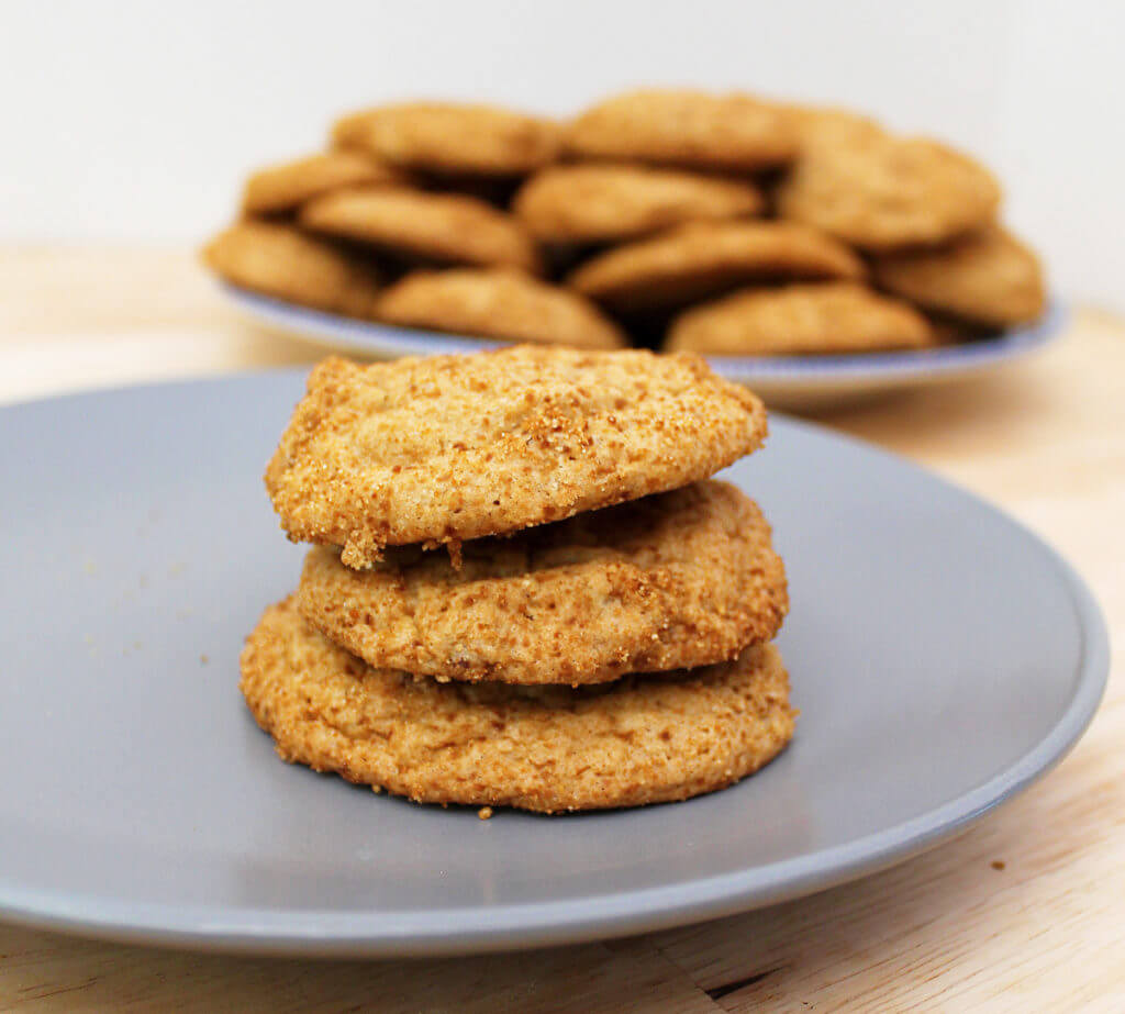 Closeup of a stack of three maple and pecan cookies with a larger plate of cookies in the background.