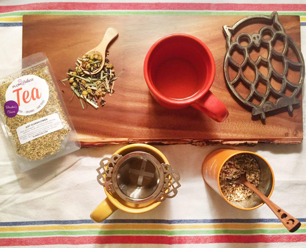 Overhead view of bags and canisters of loose leaf tea with mugs and tea infusers on a wooden board.