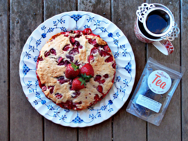 Overhead view of a strawberry buckle cake on a blue and white platter, with a cup of tea and bag of loose leaf tea on the side.