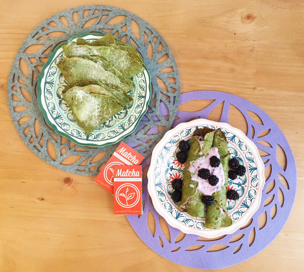 Overhead view of two plates of matcha crepes on cutout felt place mats. Two packages of matcha green tea powder sit between them.