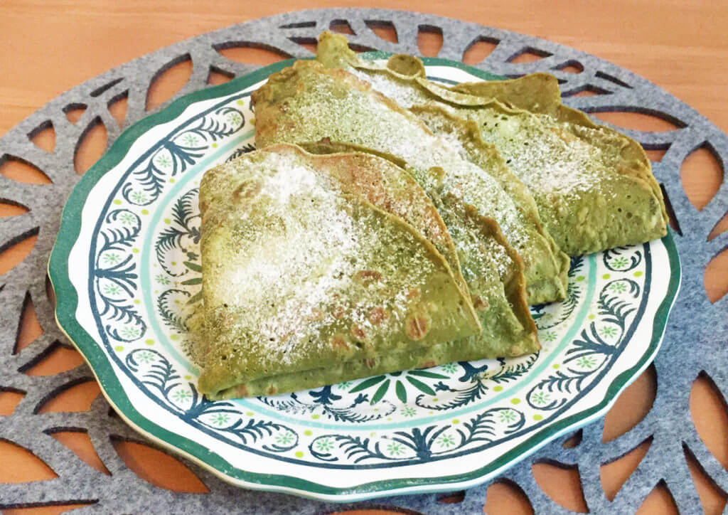 Folded matcha crepes dusted with powdered sugar sit on a plate.