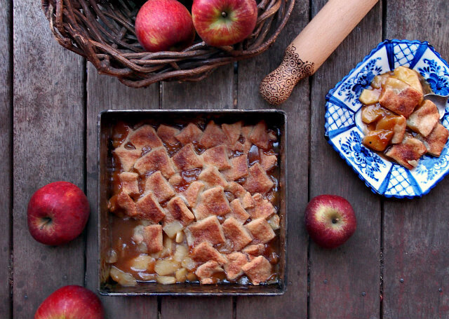 Overhead view of a square pan of apple pandowdy surrounded by apples and a wooden rolling pin.