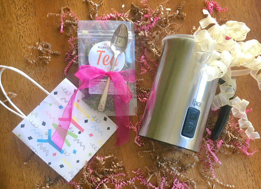 Overhead view of an electric milk frothing pitcher, a teaspoon tied to a bag of loose leaf tea with a bright pink ribbon, and a gift bag that says