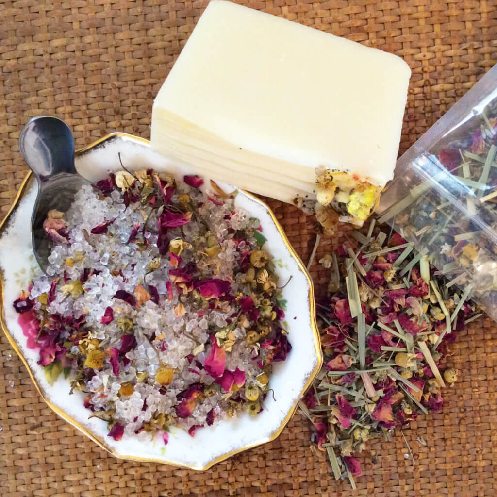 A tea spa kit of loose leaf tea, soap, and tea-infused bath salts sits on a woven mat.
