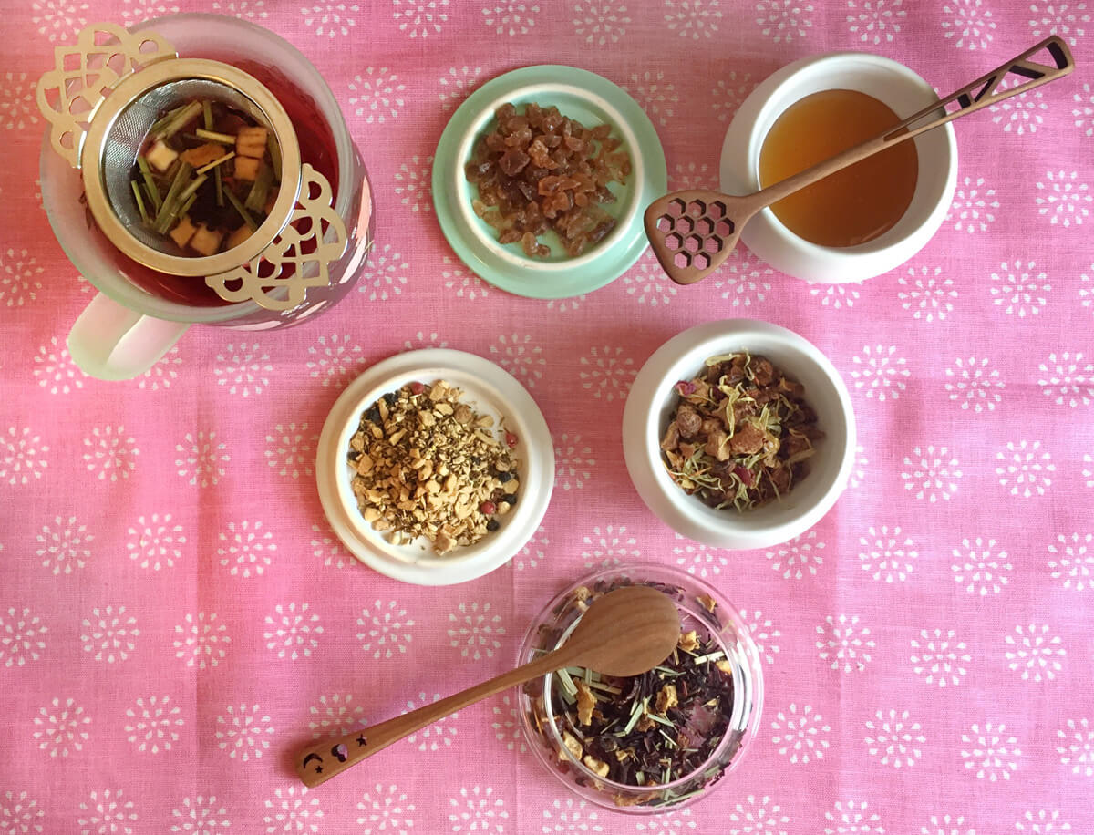Overhead view of bowls of herbal loose leaf tea, bowls of sugar and honey, and a teacup with victorian tea infuser.