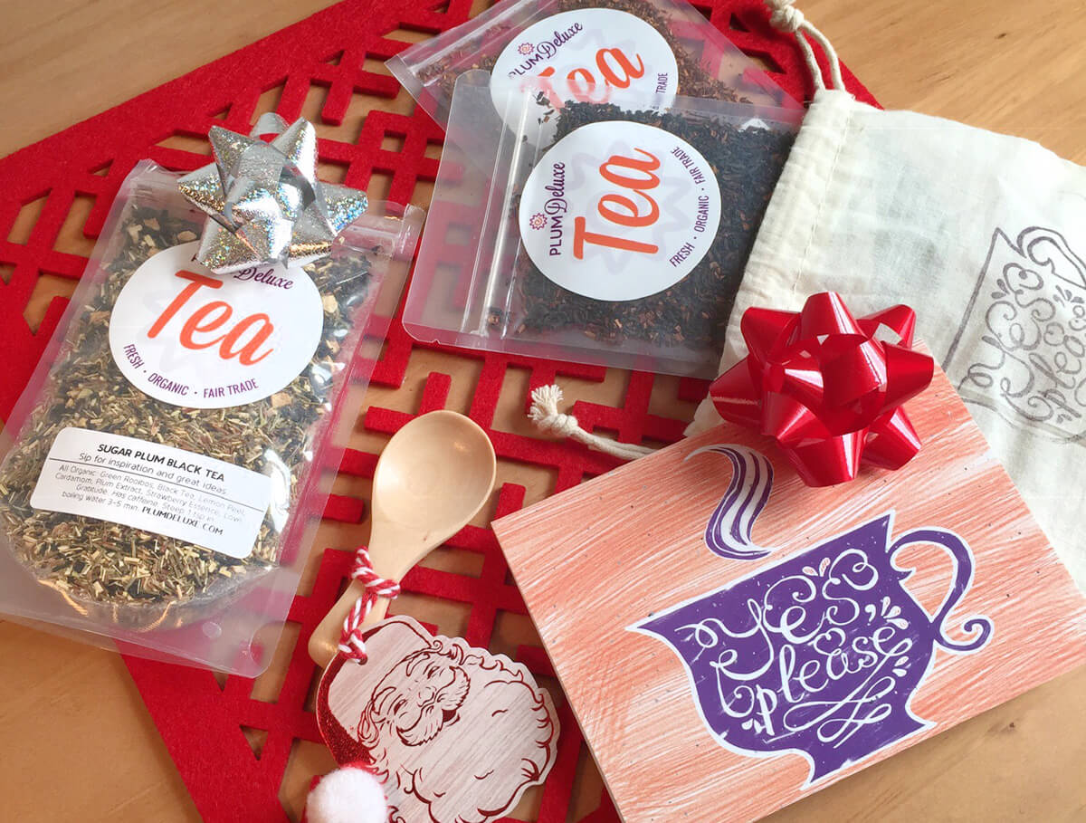"""A trio of Plum Deluxe loose leaf teas, a gift bag that says """"Yes, Please,"""" a wooden tea scoop, and a card are scattered on a red mat."""