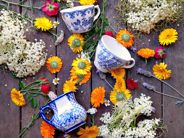 Overhead view of blue and white teacups surrounded by scattered orange, yellow, red, and white flowers on a wooden table.