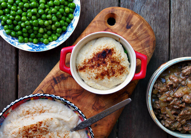 Overhead view of a shepherd's pie with cauliflower mash, surrounded by its component parts: beef gravy, green peas, and cauliflower mash.