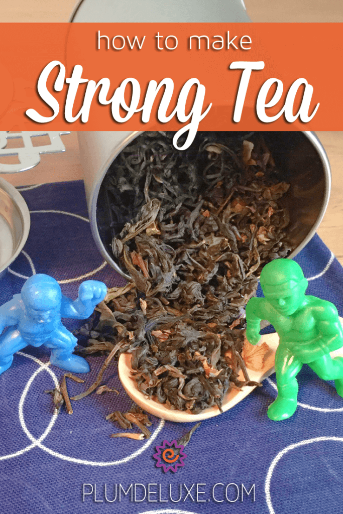 Two strong action figures stand on either side of loose leaf tea pouring out of a tin.