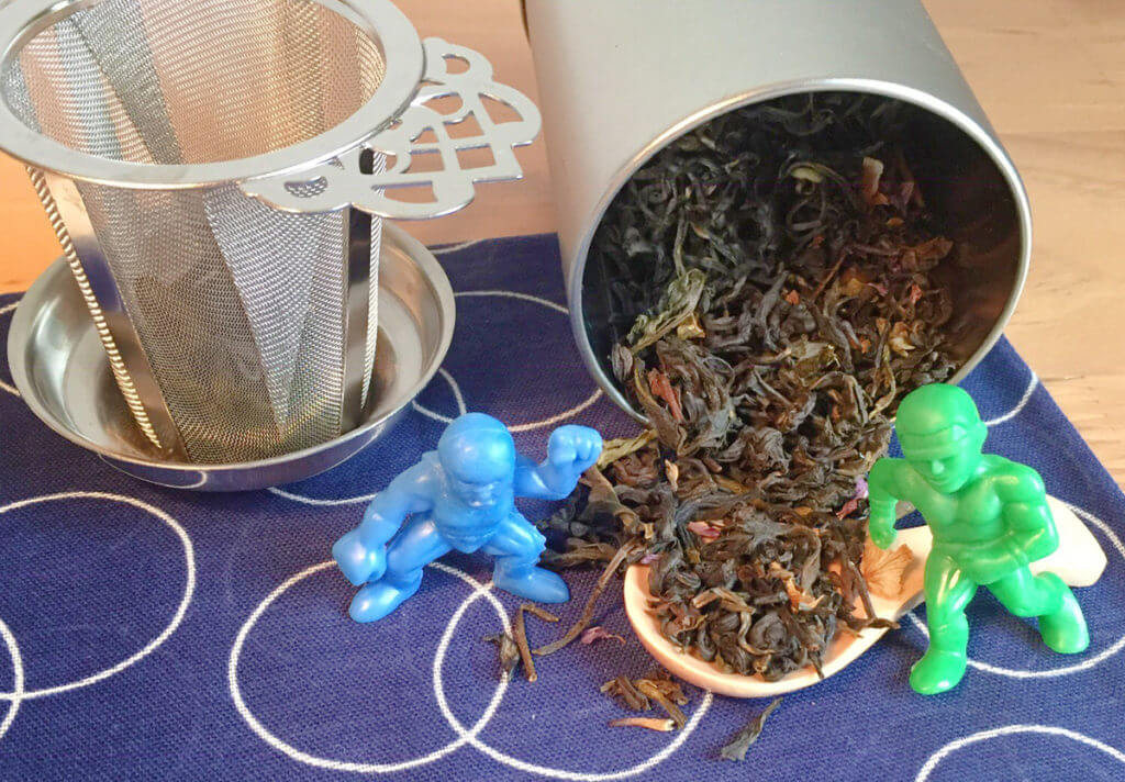 Two strong action figures stand on either side of loose leaf tea pouring out of a tin. A tea infuser sits in the background.