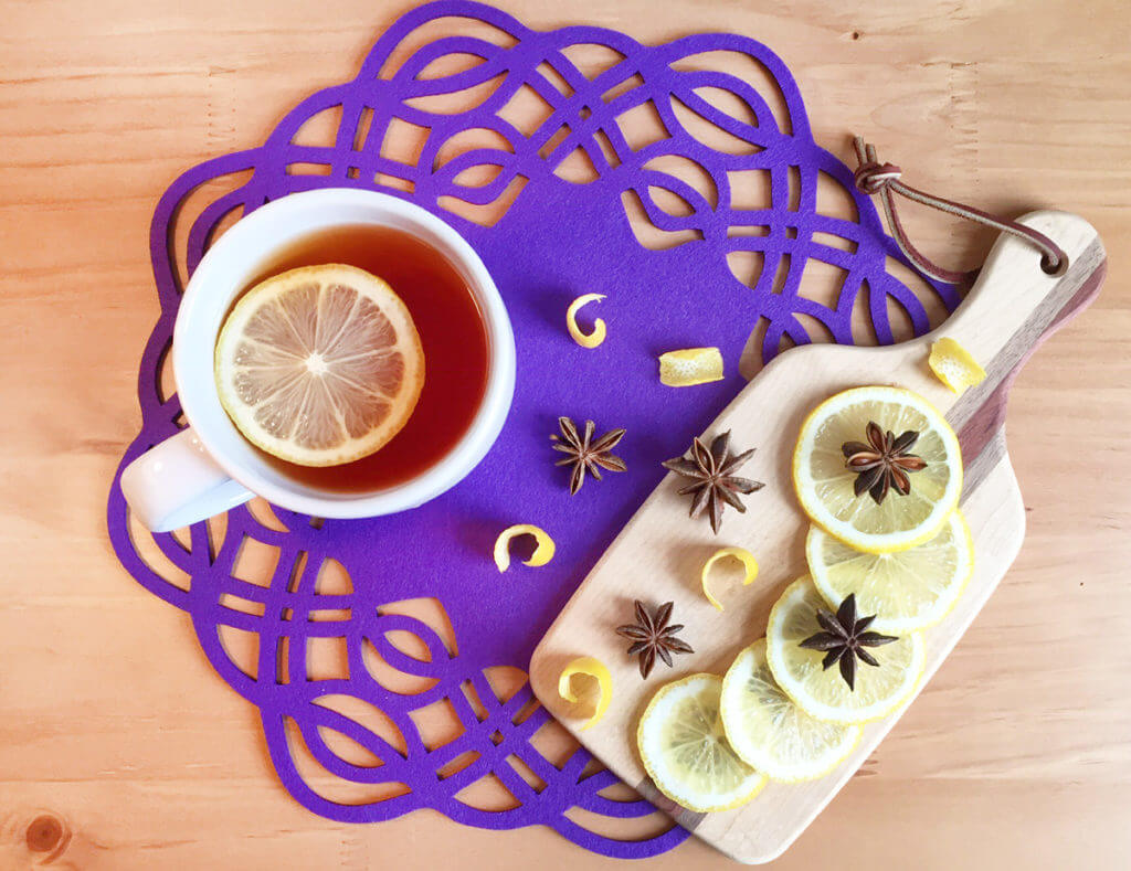 Overhead view of a white teacup of tea with a lemon slice floating on top, on a purple placemat next to a wooden cutting board with more lemon slices and anise pods.