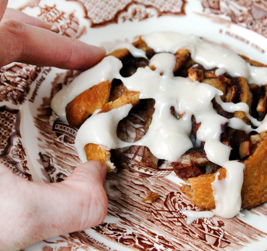A hand pulls apart a cinnamon roll with apples that is sitting on a brown and white vintage plate.