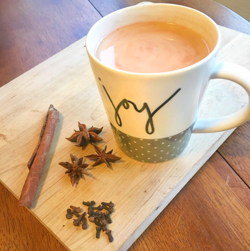 """A mug that says """"joy"""" and is filled with chai tea sits on a wooden board, surrounded by cinnamon sticks, star anise, and cloves."""