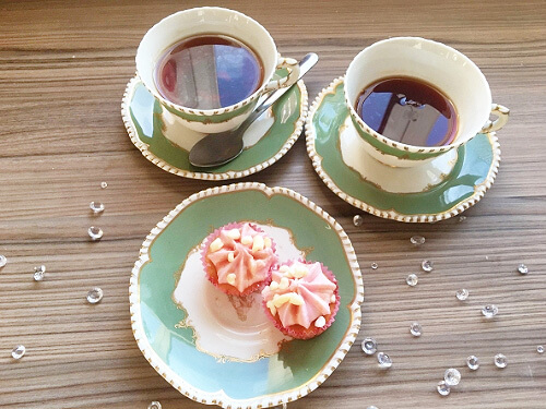 Two green and white teacups filled with tea sit beside a matching plate with two miniature cupcakes.