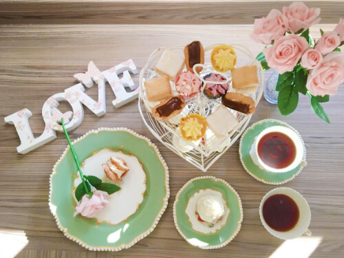 Overhead view of a warming cream tea with cups of tea, scones, and small cakes on green and white plates.