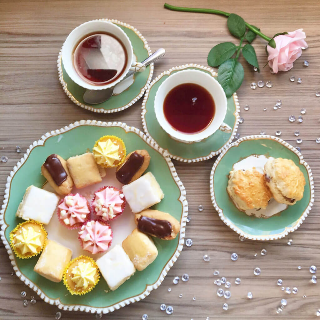 Overhead view of a warming cream tea with cups of tea, scones, and miniature baked goods served on green and white plates.