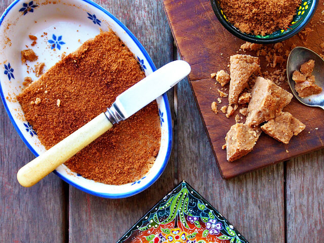 Overhead view of a pan of maple fudge dusted with maple dust, next to a wooden cutting board with dried maple syrup chunks.