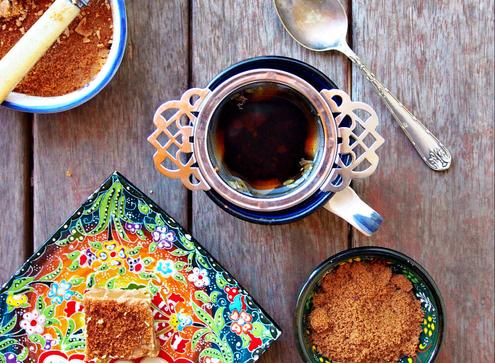A mug of tea with a Victoria tea infuser sits next to a bright floral plate with a piece of maple fudge. A small bowl of maple dust, a silver teaspoon, and a pan of maple fudge surround it, all on a wooden table.
