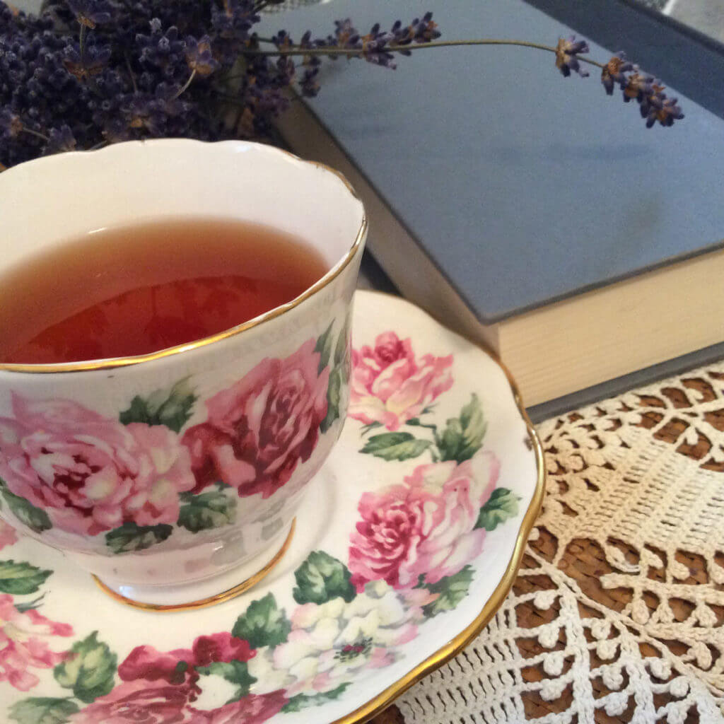A rose pattern teacup and a book with a blue cover sit on a crocheted lace doily.