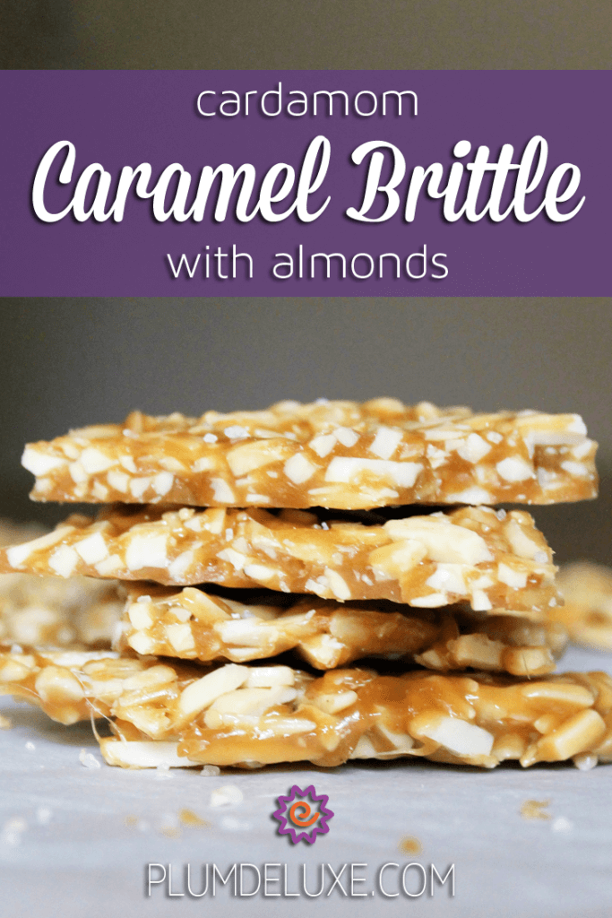 Pieces of cardamom caramel brittle with almonds are stacked on a piece of parchment paper.