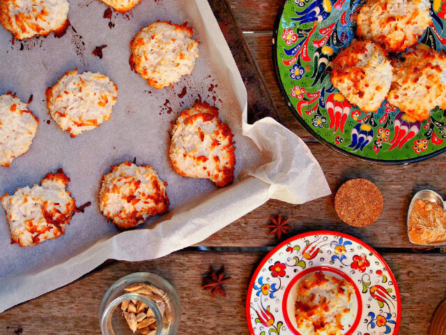 Overhead view of a baking tray and two floral plates full of gingerbread spice coconut macaroons.