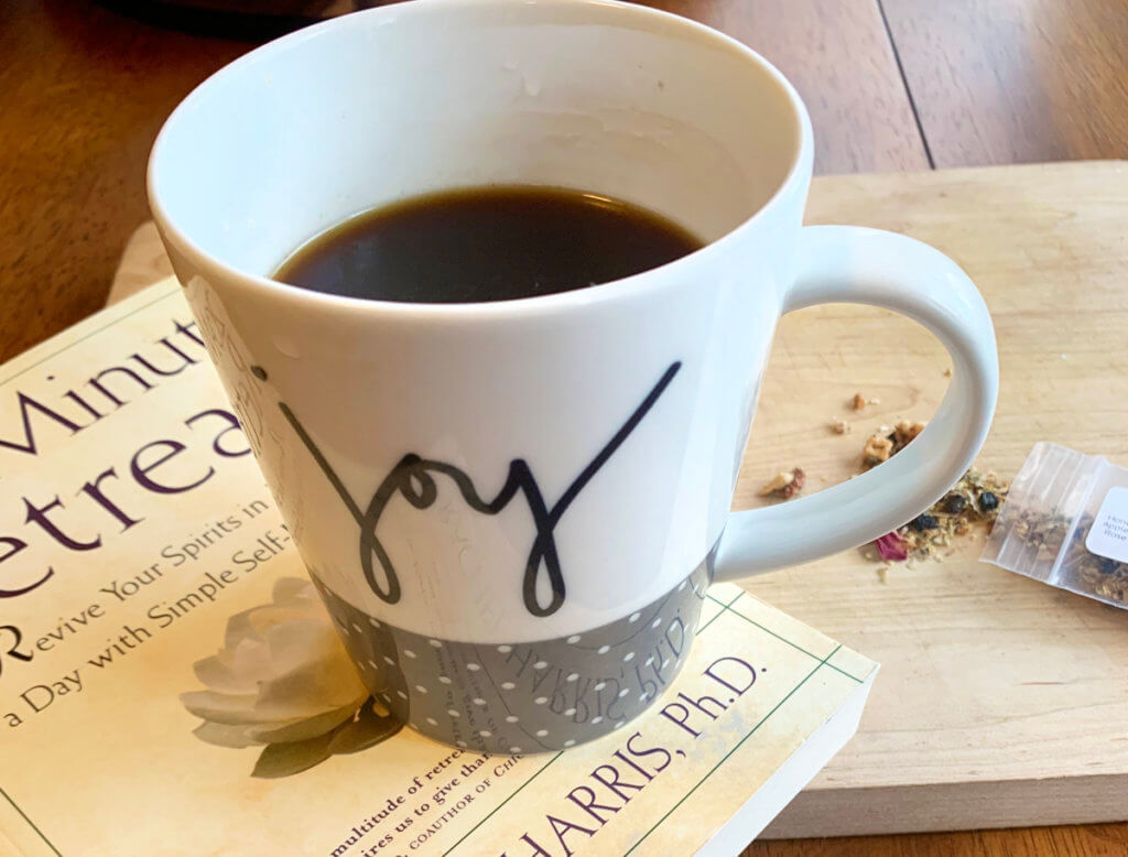 """A mug of tea with the word """"joy"""" written on it rests on top of a book."""