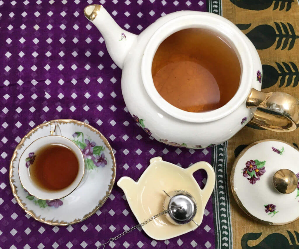 Overhead view of a white and violet teapot and teacup set on a purple and white tablecloth.